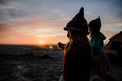Sisters playing with sparkler while camping at beach during sunset - p1166m1534183 by Cavan Images