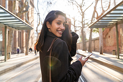 Portrait of happy young woman with smartphone on tram line - p300m2166180 by VITTA GALLERY