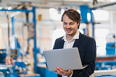 Smiling businessman using laptop while standing at industry - p300m2250782 by Daniel Ingold