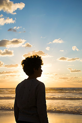 Silhouette of a boy standing on the beach at sunset  - p794m1510978 by Mohamad Itani