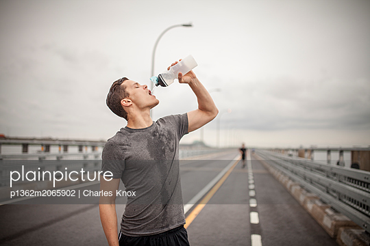 Male athlete pouring water trying to rehydrate during workout outdoors, Montreal, Quebec, Canada - p1362m2065902 by Charles Knox