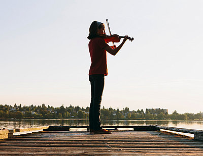 A ten year old girl playing the violin at dawn on a wooden dock. - p1100m876046f by Paul Edmondson