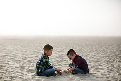 Side view of brothers making sandcastle at beach against sky during foggy weather - p1166m2066630 by Cavan Images