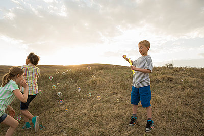 Little friends playing with soap bubbles during field trip - p1192m1044115f by Hero Images