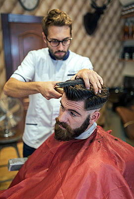 Barber cutting hair of a customer - p300m1081638f by Marco Govel