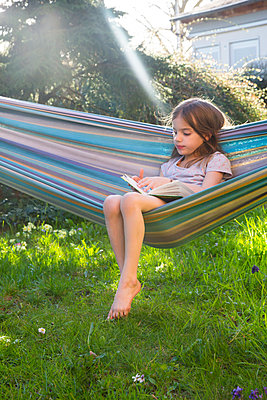 Little girl sitting on hammock in the garden reading a book - p300m1580747 von Larissa Veronesi
