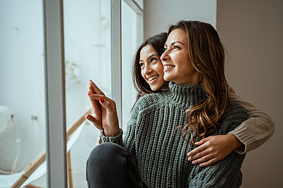 Happy mother and daughter looking through window while sitting at home - p300m2256510 by Rafa Cortés