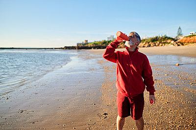 Man drinking water on seashore at beach during sunset - p300m2275615 by Kiko Jimenez