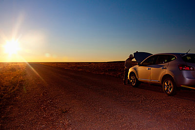 Person opening hood of car on remote road, Grand Canyon National Park, Arizona, United States - p555m1415820 by Camilo Morales