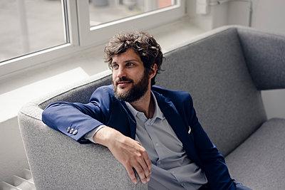 Junger Geschäftsmann sitzt auf einem Sofa - p586m1562030 von Kniel Synnatzschke
