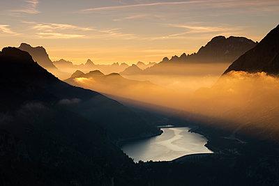 Orange light beam and mist on peaks of Dolomiti and Fedaia Pass, Cima Belvedere, Val di Fassa, Trentino-Alto Adige, Italy, Europe - p871m1221565 by Roberto Moiola