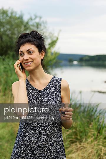 Junge Frau telefoniert mit einem Glas Wein am Ufer - p1212m1159123 von harry + lidy