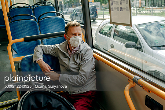 Mid adult man looking through window while traveling from bus during COVID-19 - p300m2243925 by Oxana Guryanova