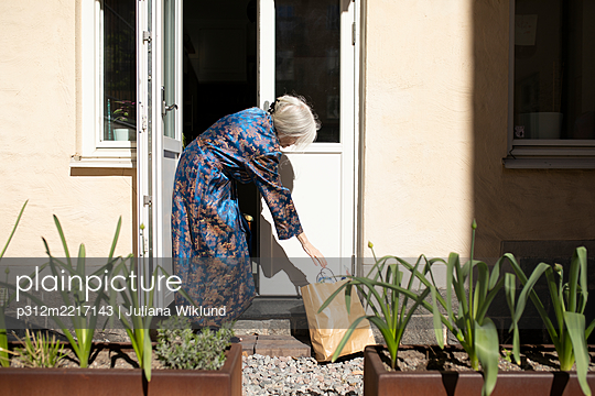 Woman reaching for paper bag in front of house - p312m2217143 by Juliana Wiklund