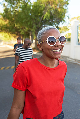 Happy young woman in sunglasses walking in street - p1023m2190231 by Trevor Adeline