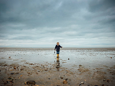 Little boy Exploring on beach at low tide - p1072m2172273 by Neville Mountford-Hoare