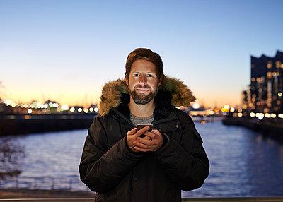 Mann mit Smartphone am Wasser - p1124m1195812 von Willing-Holtz