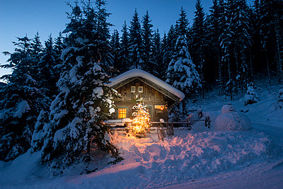 Austria, Altenmarkt-Zauchensee, sledges, snowman and Christmas tree at illuminated wooden house in snow at night - p300m2041989 by Hans Huber