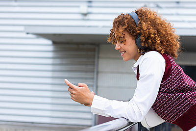 Smiling teenage girl with headphones using mobile phone while leaning on railing - p300m2267191 by NOVELLIMAGE