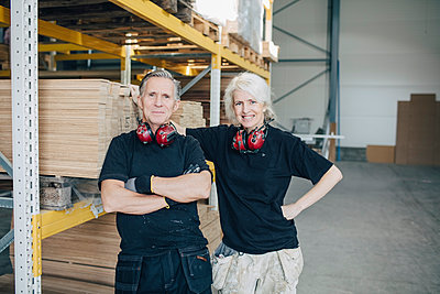 Portrait of smiling male and female workers standing by rack in industry - p426m1537025 by Maskot