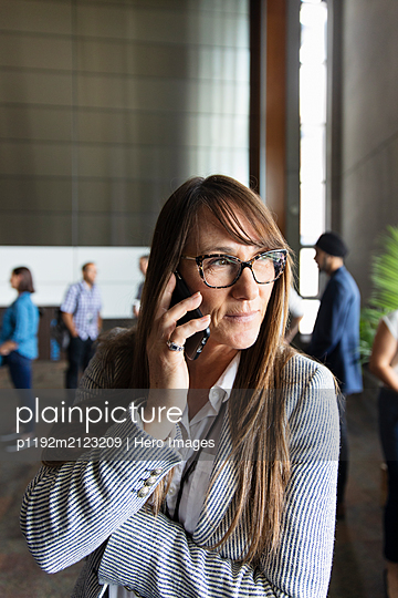 Businesswoman talking on smart phone at conference - p1192m2123209 by Hero Images