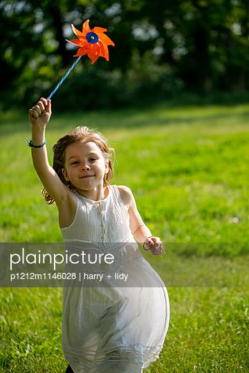 Mädchen mit Windrad in der Wiese - p1212m1146028 von harry + lidy