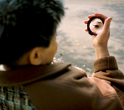 Woman with eye reflected in compact mirror - p1125m2013975 by jonlove