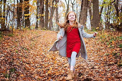 Young Red Hair Girl Playing Outside in Fall Leaves - p1166m2147084 by Cavan Images