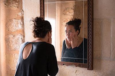 Frau betrachtet sich kritisch im Spiegel - p1396m2093594 von Hartmann + Beese