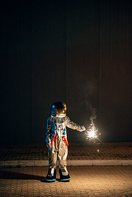Spaceman standing on a road at night holding sparkler - p300m2043159 by Vasily Pindyurin