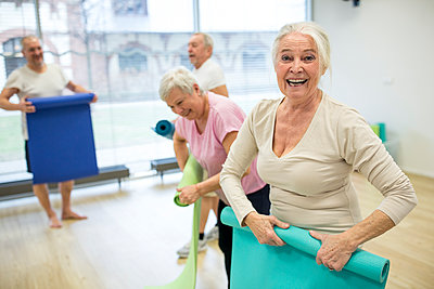 Laughing senior woman rolling up mat after yoga class - p300m2207058 by Fotoagentur WESTEND61