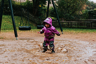 Toddler girl splashing in puddle - p312m2239730 by Jennifer Nilsson