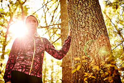 Woman in sportswear standing in forest - p343m2046851 by Josh Campbell