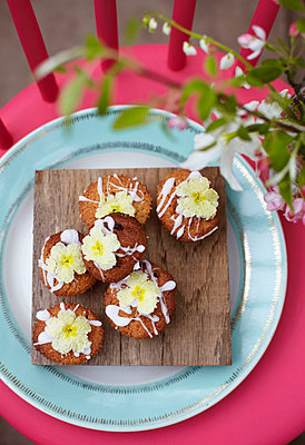 Iced cup cakes on a wooden board with drizzled icing and primroses - p349m2167879 by Sussie Bell
