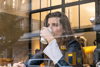 Young woman enjoying hot drink in cafe - p429m2077877 by Tamboly
