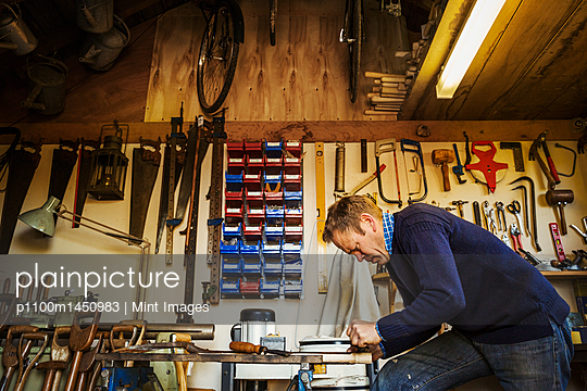 Man standing in a garden workshop surrounded by tools hanging from beams and a stack of garden tools propped up. - p1100m1450983 by Mint Images