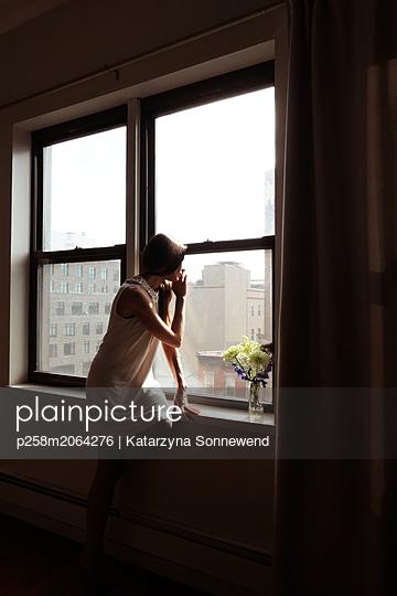Woman in window with flower - p258m2064276 von Katarzyna Sonnewend
