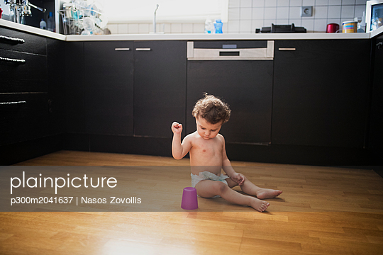 Baby boy sitting on floor in the kitchen playing with plastic cup - p300m2041637 von Nasos Zovoilis