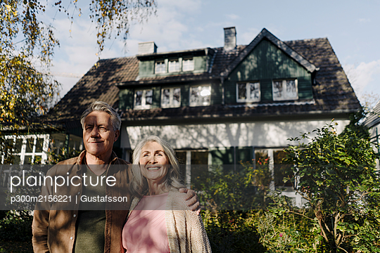 Senior couple in garden of their home in autumn - p300m2156221 by Gustafsson