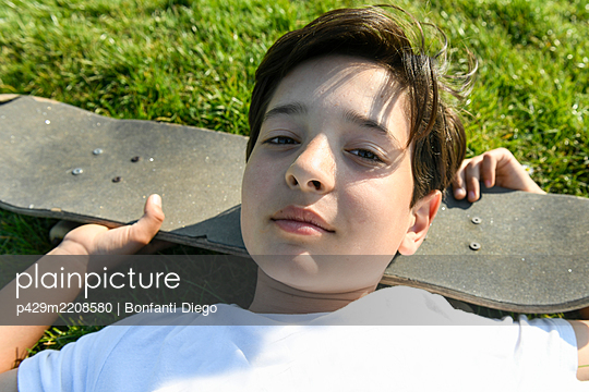 Boy with brown hair lying on grass, head resting on skateboard, looking at camera. - p429m2208580 by Bonfanti Diego