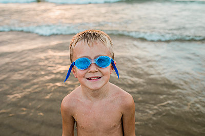 Portrait of shirtless boy wearing swimming goggles while standing on shore at beach - p1166m1569008 by Cavan Images