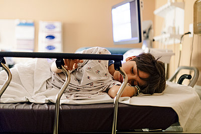 Sad thoughtful boy resting on bed in hospital - p1166m2067531 by Cavan Images