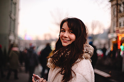 Portrait of happy teenage girl in warm clothing standing in city - p1166m2189668 by Cavan Images