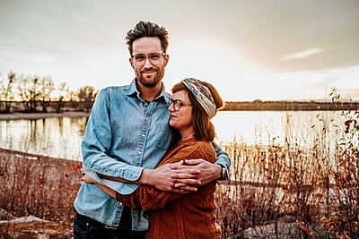 Happy couple hugging near a lake in Denver CO on a autumn evening - p1166m2208502 by Cavan Images