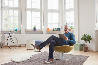 Mature man at home sitting in chair using digital tablet - p300m1153678 by Rainer Berg