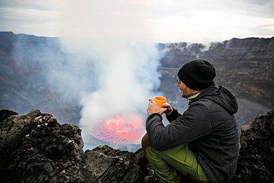 Africa, Democratic Republic of Congo, Virunga National Park, Man sittiing over Nyiragongo volcano crater - p300m2005432 by realitybites
