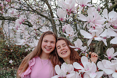 Happy female friends by magnolia trees in park - p300m2257033 by Oxana Guryanova