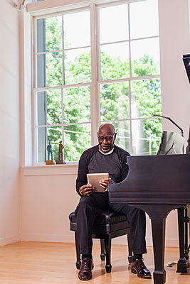Man sitting at piano using digital tablet near window - p555m1303742 by Strauss/Curtis
