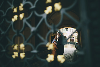 Caucasian couple embracing in street behind gate - p555m1532628 by Kateryna Soroka