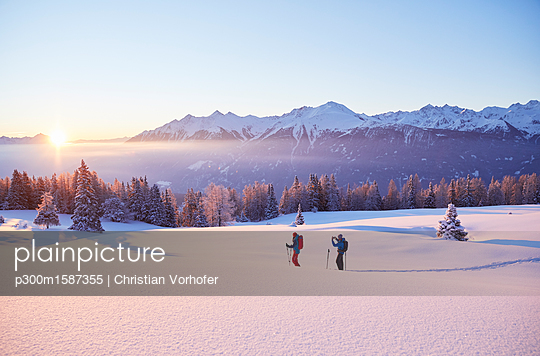 Austria, Tyrol, couple snowshoeing at sunrise - p300m1587355 von Christian Vorhofer